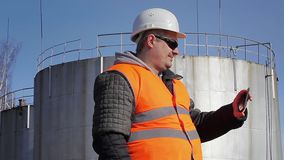 Engineer filmed with tablet PC near oil tank stock video footage