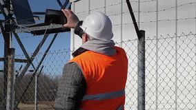 Engineer filmed with tablet PC at outdoors near metal structures stock video