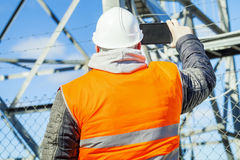 Engineer filmed with tablet PC at outdoors near metal structures. In autum day stock image