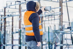 Engineer filmed with tablet PC at power plants in winter. Day Stock Image