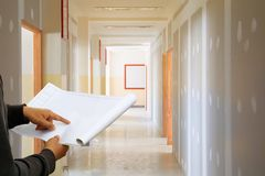 Engineer finger point on paper plan blueprint in check building technician place construction site gypsum board wall interior. Background stock photo