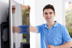 Engineer Fitting Curved Screen Television In Home. Engineer Fits Curved Screen Television In Home Royalty Free Stock Photography