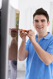 Engineer Fitting Curved Screen Television In Home. Engineer Fits Curved Screen Television In Home Stock Photo