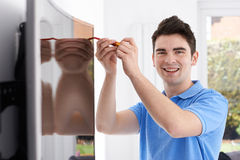 Engineer Fitting Curved Screen Television In Home. Engineer Fits Curved Screen Television In Home Royalty Free Stock Image