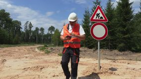 Engineer fix road signs and talking on phone stock footage