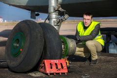 Engineer fixing aircraft's wheel Royalty Free Stock Image