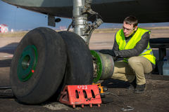 Engineer fixing aircraft's wheel Stock Image