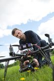 Engineer Fixing Camera On UAV Helicopter. Portrait of young engineer fixing camera on UAV helicopter in park stock photo