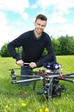 Engineer Fixing Propeller Of Octocopter. Portrait of young engineer fixing propeller of octocopter in park stock images