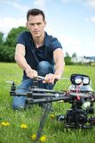 Engineer Fixing Propeller Of UAV Spy Drone. Portrait of confident young engineer fixing propeller of UAV spy drone in park stock photos