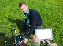 Engineer Fixing UAV Helicopter in Park. High angle view of happy young engineer fixing UAV helicopter in park stock images