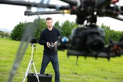Engineer Flying UAV Helicopter in Park. Young male engineer flying  UAV helicopter with remote control in park Royalty Free Stock Photography