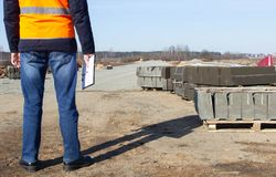 An engineer with a folder in the signal vest checks the quality of the curb for the construction of a new road, inspector royalty free stock photos