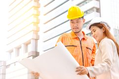 Engineer and foreman looking at constructed paper blueprint plan. S at construction site royalty free stock photography