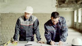 The engineer and foreman in a protective helmet make notes in the construction drawings, the men are in a factory that stock video