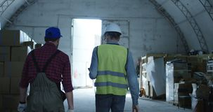 Engineer and foreman talking in a warehouse. Medium shot of engineer and foreman talking in a warehouse stock video