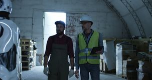 Engineer and foreman talking in a warehouse. Medium shot of engineer and foreman talking in a warehouse stock video footage