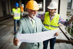 Engineer, foreman and worker discussing in building construction site. Engineer, foreman and worker discussing and working in building construction site royalty free stock images