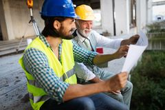 Engineer, foreman and worker discussing in building construction site stock images