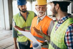 Engineer, foreman and worker discussing in building construction site. Engineer, foreman and worker discussing and working in building construction site royalty free stock photos
