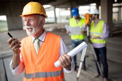 Engineer, foreman and worker discussing in building construction site stock photography