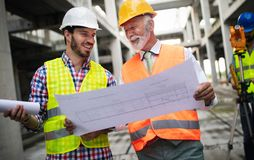 Engineer, foreman and worker discussing in building construction site. Engineer, foreman and worker discussing and working in building construction site royalty free stock image