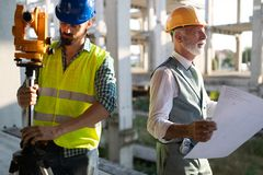 Engineer, foreman and worker discussing in building construction site royalty free stock photography