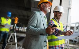Engineer, foreman and worker discussing in building construction site stock image