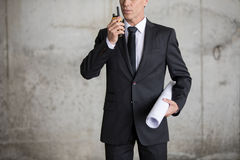 Engineer in formal wear holding blueprint and using walkie-talkie Stock Images