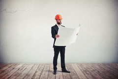Engineer in a formal wear looking blueprints Royalty Free Stock Images