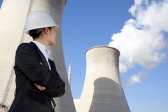 Engineer in front of cooling towers Stock Photography