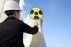Engineer in front of cooling towers with sign Royalty Free Stock Image