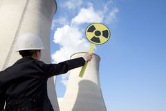 Engineer in front of cooling towers with sign Stock Photography