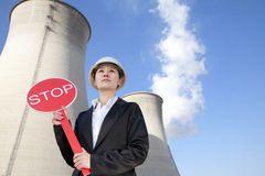 Engineer in front of cooling towers with stop sign Stock Photography