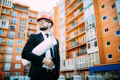 Engineer in front of modern building with plan looking at blueprint Stock Photos