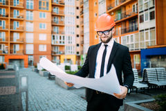 Engineer in front of modern building with plan looking at blueprint. Engineer in front of modern building with plan Stock Photography