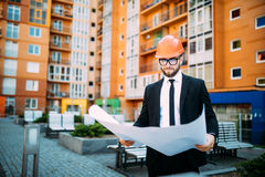 Engineer in front of modern building with plan looking at blueprint. Engineer in front of modern building with plan Stock Photos