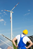 Engineer in front of solar panels looks at wind turbine Stock Image