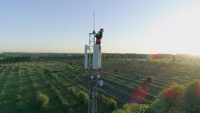 Engineer with gadget connected a mobile communication on radio telecommunication tower on background of blue sky with