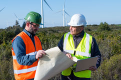 Engineer and geologist consult close to wind turbines in the countryside. An engineer and geologist consult close to wind turbines in the countryside Royalty Free Stock Images