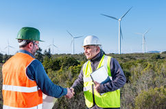 Engineer and geologist consult close to wind turbines in the countryside Royalty Free Stock Photos