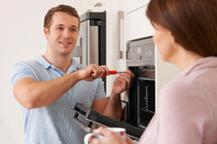 Engineer Giving Advice To Woman On Kitchen Repair. Engineer Gives Advice To Woman On Kitchen Repair Stock Photography