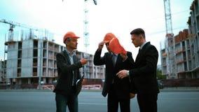 Engineer giving businessmen helmets stock video