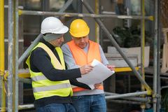 Engineer giving colleague arrangements about a new construction site. Outdoors stock photos