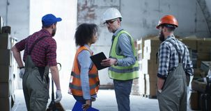 Engineer giving out instructions in a warehouse. Medium long shot of engineer giving out instructions in a warehouse stock footage