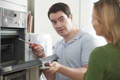 Engineer Giving Woman Advice On Kitchen Repair. Engineer Giving Woman Advice On Oven Repair Royalty Free Stock Images