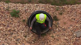 Engineer going out from flow pipe. In summer day stock video footage