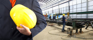 Engineer hand holding yellow helmet. For workers security against the background of steel pipe packing factory Stock Image