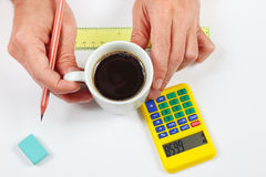 Engineer hands holding a cup of coffee over workplace Stock Images