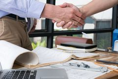 Engineer handshaking for successful deal in construction plan. a. Engineer handshaking for successful deal in construction plan. young architect shake hand for Royalty Free Stock Photo
